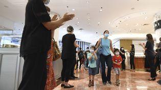 Des clients masqués entrant dans les galeries Lafayette, à Paris, le 30 mai 2020. (ALAIN JOCARD / AFP)