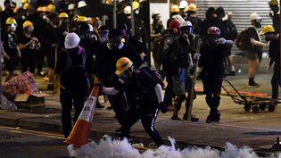 Des manifestants recouvrent une bombe de gaz lacrymogène avec un cône de chantier lors d'affrontements avec les forces de l'ordre, le 28 juillet 2019 à Hong Kong. (ANTHONY WALLACE / AFP)