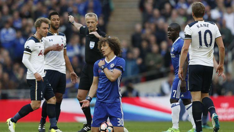 Le Brésilien de Chelsea, David Luiz, à terre face aux joueurs de Tottenham, sous le regard de l'arbitre. (ADRIAN DENNIS / AFP)