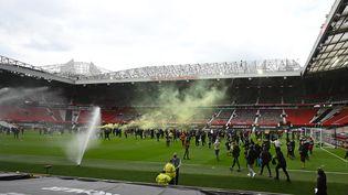 Des supporters de Manchester United en colère contre les propriétaires du club anglais protestent sur la pelouse du stade d'Old Trafford avant la rencontre les Red Devils et Liverpool, dimanche 2 mai 2021. (OLI SCARFF / AFP)