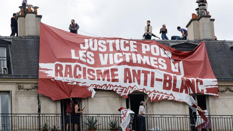 """Des activites de Génération identitaire déploient une banderiole où il est inscrit """"Justice pour les victimes du racisme anti-blanc"""",place de la République à Paris, le 13 juin 2020. (THOMAS SAMSON / AFP)"""