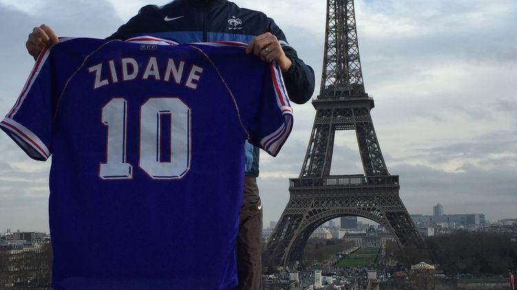 Le collectionneur Olivier Démolis pose avec son maillot de Zinédine Zidane, porté pendant la finale de la Coupe du monde 1998, devant la Tour Eiffel, à Paris. (OLIVIER DEMOLIS / DR)
