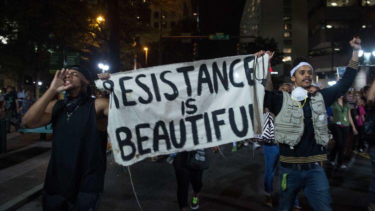 """Des manifestants brandissent une banderole """"La résistance est belle"""", dans les rues de Charlotte, en Caroline du Nord (Etats-Unis), le 22 septembre 2016. (NICHOLAS KAMM / AFP)"""