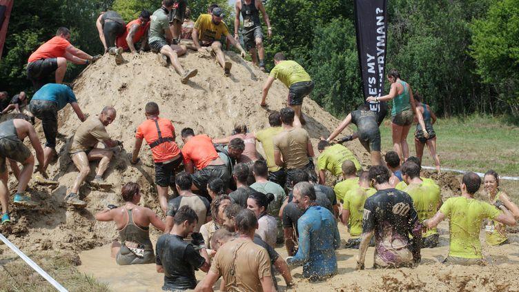 """Des participants plongés dans la boue lors de l'épreuve du """"Mud Day"""" de Levens (Alpes-Maritimes), le 20 juin 2015. (MAXPPP)"""