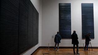A droite, deux des trois tableaux que Pierre Soulages vient de peindre, accrochés au Louvre, au Salon carré (6 décembre 2019) (FRANCOIS GUILLOT / AFP)