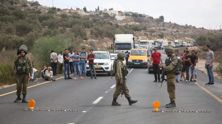 Des soldats israéliens bloquent une route,le 7 octobre 2018, après une attaque meurtrière dansla zone industrielle de Barkan en Cisjordanie. (ISSAM RIMAWI / ANADOLU AGENCY / AFP)