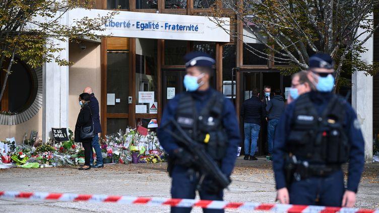 Des policiers devant le collège Le Bois d'Aulne, à Conflans-Sainte-Honorine (Yvelines), où enseignait Samuel Paty, le 19 octobre 2020. (ANNE-CHRISTINE POUJOULAT / AFP)