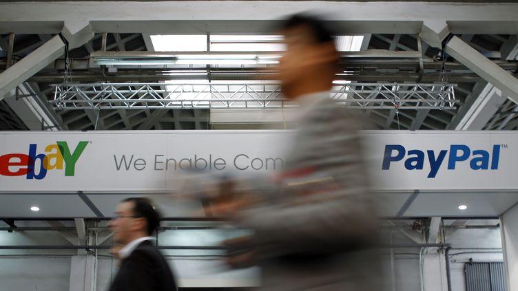 Des visiteurs passent devant une bannière du stand eBay et PayPallors d'un salon de la téléphonie mobile, à Barcelone (Espagne), le 28 février 2012. (ALBERT GEA / REUTERS)