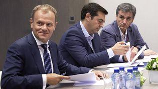 Le président du Conseil européen, Donald Tusk, aux côtés du Premier ministre grec, Alexis Tsipras, et du ministre des Finances grec, Euclide Tsakalotos, lors d'un sommet des chefs d'Etat de la zone euro, à Bruxelles (Belgique), le 12 juillet 2015. (COUNCIL OF THE EUROPEAN UNION / ANADOLU AGENCY / AFP)
