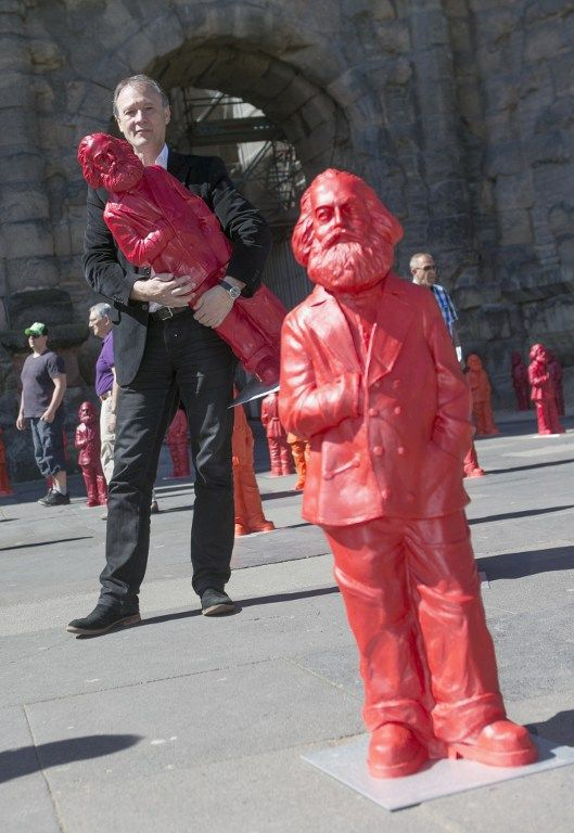 L'artiste allemand Ottmar Hoerl pose avec une des statues de Karl Marx. Il a installé 500 statues pour le 195e anniversaire de cette figure du communisme  (THOMAS WIECK / AFP)