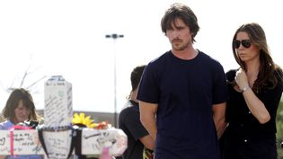 L'acteur Christian Bale et sa femme Sandra Blažić se recueillent devant le mémorial dressé en hommage aux 12 personnes tuées lors d'une fusillade dans un cinéma d'Aurora (Colorado), le 24 juillet 2012. (JOSHUA LOTT / GETTY IMAGES NORTH AMERICA)