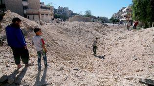 Des enfants marchent dans les décombres à Apel (Syrie), après un bombardement, le 24 septembre 2016. (JAWAD AL RIFAI / ANADOLU AGENCY / AFP)