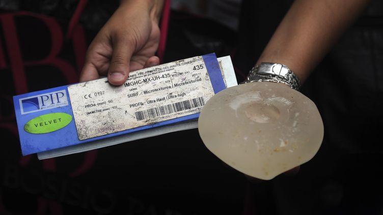 Une femme montre un certificat et un implant mammaire de la marque Poly Implant Prothèse (PIP) à Caracas (Venezuela), le 6 janvier 2012. (JUAN BARRETO / AFP)