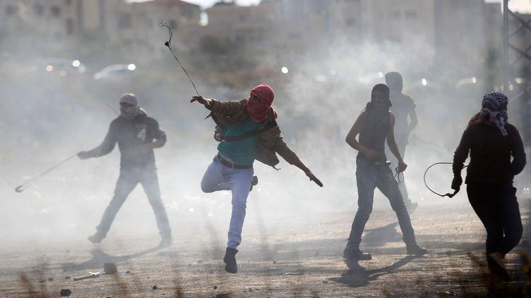 Un manifestant palestinien utilise une fronde pour lancer des pierres sur les soldats israéliens près de la colonie juive de Beit El, près de Ramallah, le 29 octobre 2015. (APA IMAGES / SIPA)