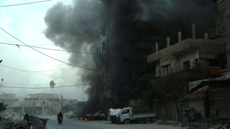 De la fumée s'échappe d'un immeuble bombardé dans la Ghouta orientale, en Syrie, le 10 mars 2018. (HAMZA AL-AJWEH / AFP)