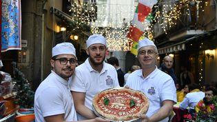 Des pizzaïolos posent à Naples (Italie), le 7 décembre 2017, pour fêter la décision de l'Unesco de faire entrer la pizza au patrimoine de l'humanité (TIZIANA FABI / AFP)