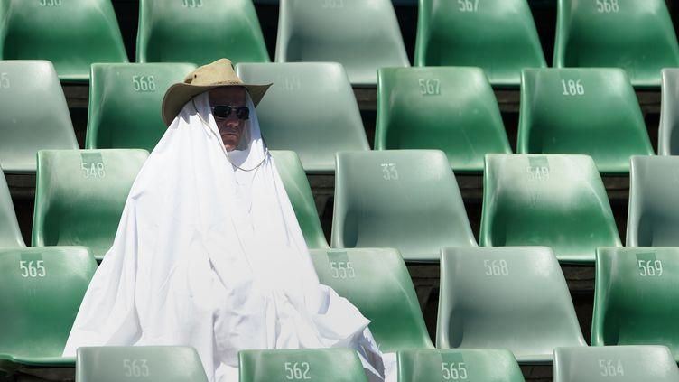 Dans les tribunes, les spectateurs se font rares. Et eux bravent la chaleur sont équipés. (WILLIAM WEST / AFP)