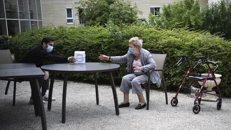 Une femme recevant un cadeau de son petit-fils dans un Ehpad de Saint-Maur-des-Fossés (Val-de-Marne) en juin 2020. (ANNE-CHRISTINE POUJOULAT / AFP)