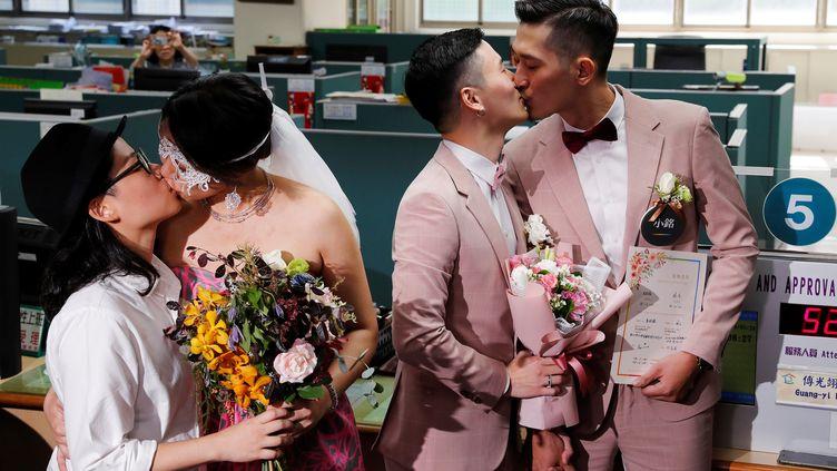Deux couples taïwanais s'embrassent après avoir fait enregistrer leur mariage civil à Taipei, capitale de Taïwan, le 24 mai 2019, jour d'entrée en vigueur de l'autorisation du mariage homosexuel dans le pays. (TYRONE SIU / REUTERS)