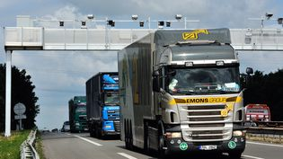 Des camions passent sous un portique destiné à l'écotaxe en juin 2013, avant l'abandon du projet (PHILIPPE HUGUEN / AFP)