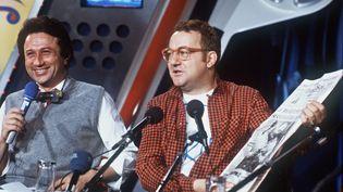 """L'humoriste français Coluche (D) tient un exemplaire de France Soir au côté de l'animateur de télévision Michel Drucker (G), avec qui il participe à l'émission """"Studio 1"""", le 6 avril 1984 dans les studios de la radio Europe 1, à Paris. (AFP PHOTO)"""