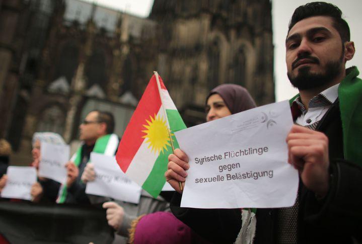"""Des Syriens (portant un drapeau kurde), manifestent contre les violences sexuelles. """"Réfugiés syriens contre le harcèlement sexuel"""", est-il écrit, en allemand, sur cette pancarte, à Cologne, le 14 janvier 2016. (OLIVER BERG / DPA / AFP)"""