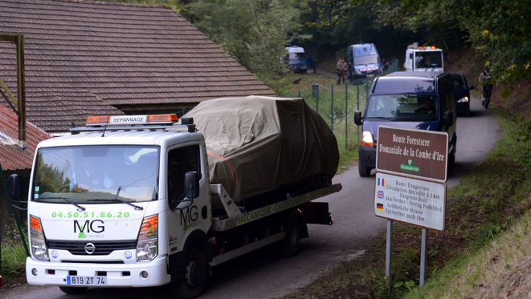 Un camion transporte le véhicule dans lequel trois personnes ont été retrouvées mortes au côté d'un cycliste à Chevaline (Haute-Savoie), le 6 septembre 2012. (PHILIPPE DESMAZES / AFP)