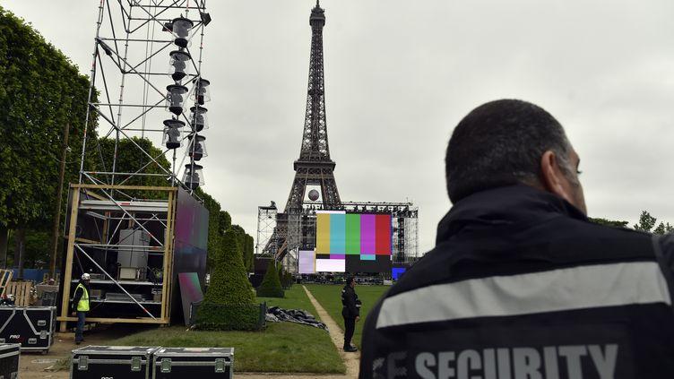 """Un agent de sécurité observe l'installation de la """"fan zone"""" de Paris, sur le Champ-de-Mars, le 3 juin 2016. (ALAIN JOCARD / AFP)"""
