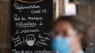 Une femme portant un masque installée sur la terrasse d'un bar à Nantes, le 20 juillet 2020. (LOIC VENANCE / AFP)