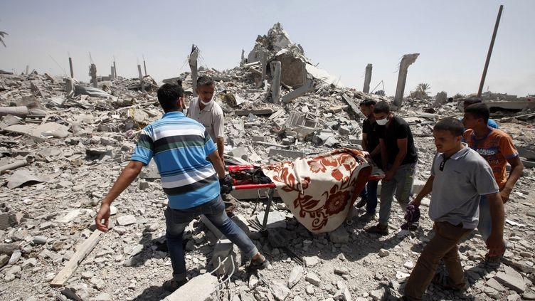 Des Palestiniens portent le corps d'un homme, le 1er août 2014, à Khuza'a, dans la bande de Gaza. (CITIZENSIDE/ELOISE BOLLACK / AFP)