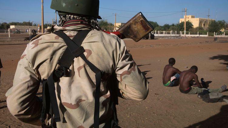Un soldat malien surveile deux jihadistes présumés à Gaoau Mali, le 22 février 2013. (JOEL SAGET / AFP)