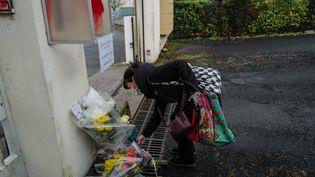 Une femme dépose des fleurs devant la gendarmerie d'Ambert (Puy-de-Dôme), le 23 décembre 2020. (OLIVIER CHASSIGNOLE / AFP)