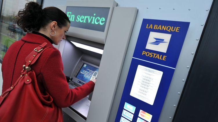 Une cliente retire de l'argent à un distributeur de la Banque postale à Caen, le 22 décembre 2008. (MYCHELE DANIAU / AFP)