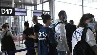 Des soignants volontaires du CHRU de Nancy attendent à l'aéroport d'Orly près de Paris le 20 août 2021 pour embarquer à bord d'avions en direction de Martinique et de Guadeloupe. (STEPHANE DE SAKUTIN / AFP)