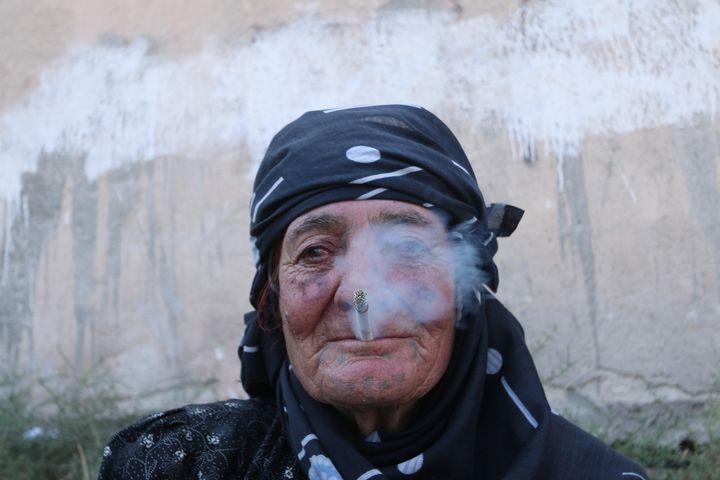 Une habitante de Manbij (Syrie) fume après la libération de la ville par lesForces démocratiques syrienne. (RODI SAID / REUTERS)