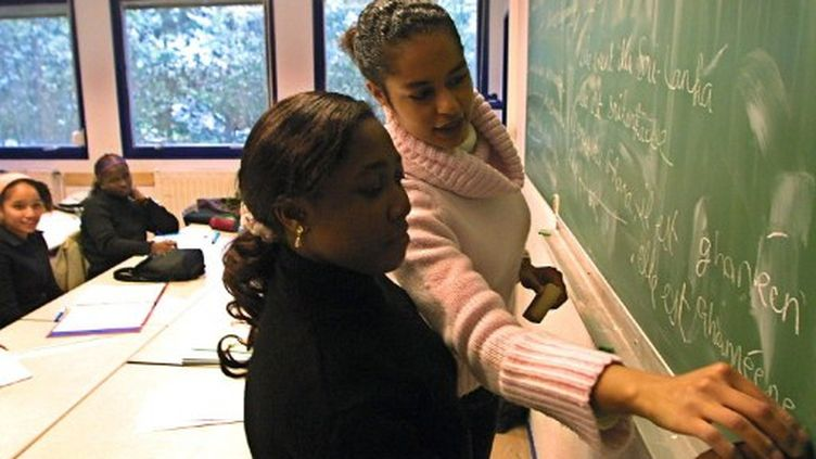 Un professeur de français corrige l'exercice d'une de ses élèves au lycée Le Corbusier d'Illkirch-Graffenstaden (2001). (AFP - Thomas Wirth)