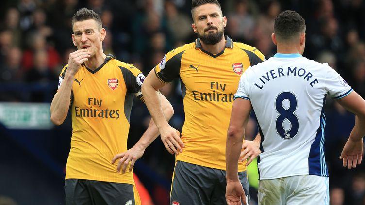 Laurent Koscielny et Olivier Giroud, lors de la défaite d'Arsenal face à WBA (1-3). (LINDSEY PARNABY / AFP)