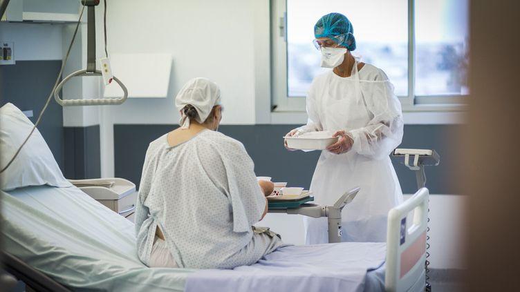 Une infirmière auprès d'un patient dans l'unité Covid du CHU de Limoges (Haute-Vienne), le 3 décembre 2020. (BURGER / PHANIE / AFP)