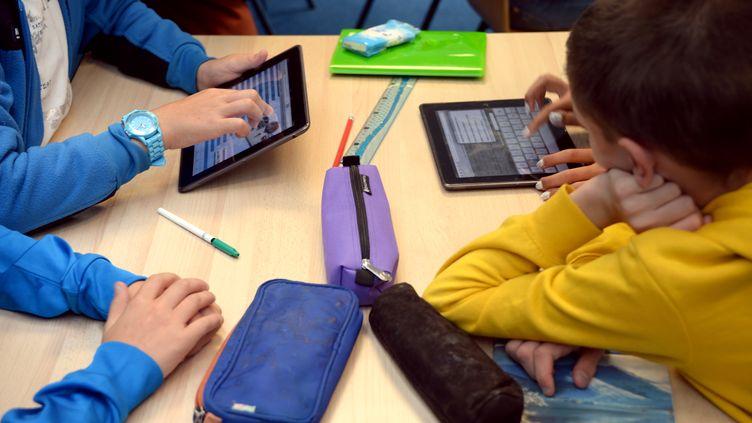 Des enfants s'initient à l'informatique sur des tablettes. (DAMIEN MEYER / AFP)