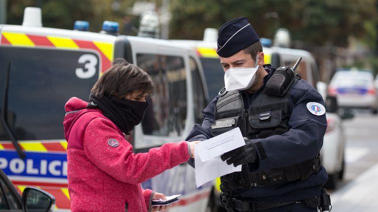 Un fonctionnaire de police contrôle une passante, dans une rue de Toulouse (Haute-Garonne), le 17 mars 2020. (FREDERIC SCHEIBER / HANS LUCAS / AFP)