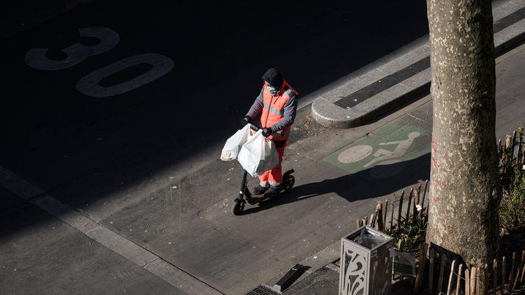 Un homme photographié sur son scooter électrique dans les rues de Paris désertées en raison du confinement, le 6 avril 2020. (JOEL SAGET / AFP)