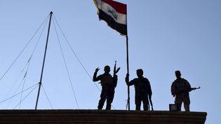 21 décembre 2015, des soldats irakiens plantent le drapeau national sur un bâtiment gouvernemental à Ramadi, 115 km à l'ouest de Bagdad (AP / SIPA)