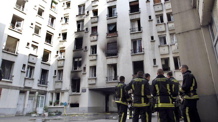 Des pompiers dans la cour d'un immeuble du 20e arrondissement de Paris dévasté par un incendie, le 27 mai 2012. (THOMAS SAMSON / AFP)