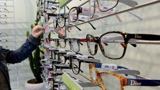 Une personne choisie des lunettes chez un opticien, à Béthune (Pas-de-Calais), le 9 mai 2014. (DENIS CHARLET / AFP)