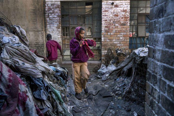 Entre deux immeubles squattés où vivent des migrants africains, Guguleto (8 ans) traverse la cour jonchée de détritusdans le centre-ville de Johannesburg (Afrique du Sud). (JONATHAN TORGOVNIK / THE VERBATIM AGENCY)