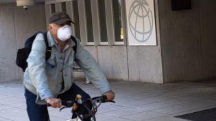 Un homme masqué passe en vélo devant un des bâtiments de la Banque mondiale à Washington (Etats-Unis), le 15 avril 2020. (SAUL LOEB / AFP)