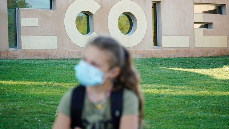 Une jeune fille portant un masque chirurgical devant une école. (MAXPPP)