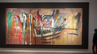 """Un visiteur contemple la toile géante """"Sans titre"""" de Basquiat, le 19 avril 2016 à New York  (Mary Altaffer / AP / SIPA)"""