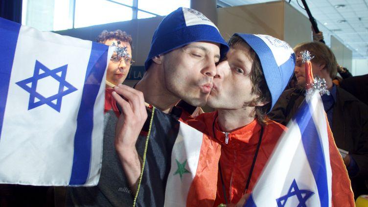 """Les chanteurs Guy Assif et Roy Arad, membres du groupe """"Ping Pong"""", représentant d'Israël au concours Eurovision, s'embrassent et tiennent des drapeaux israéliens et syriens, à Stockholm (Suède), le 12 mai 2000. (JONAS EKSTROMER / SCANPIX SWEDEN / AFP)"""