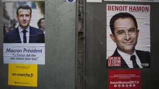 Des photos de Benoît Hamon et Emmanuel Macron sont collées sur des panneaux électoraux parisiens, le 10 avril 2017, à deux semaines du premier tour de l'élection présidentielle. (ROMANE VERCHERE / SIPA)